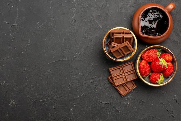 Vista superior de primer plano de chocolate en la mesa fresas en un plato tazón de fuente de crema de chocolate y barras de chocolate en el lado derecho de la mesa