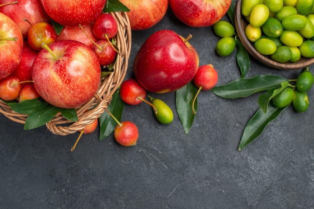 Vista superior de primer plano cítricos mandarinas cerezas manzanas cítricos con hojas en el recipiente