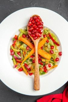 Vista superior de primer plano cuchara de ensalada de verduras de granada con semillas de granadas