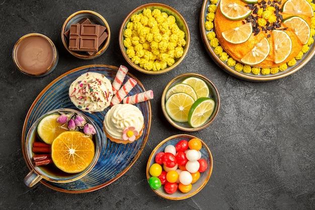 Vista superior de primer plano dulces en el plato los apetitosos cupcakes una taza de pastel de té de hierbas con naranja y tazones de limas, caramelos de chocolate y crema de chocolate sobre la mesa