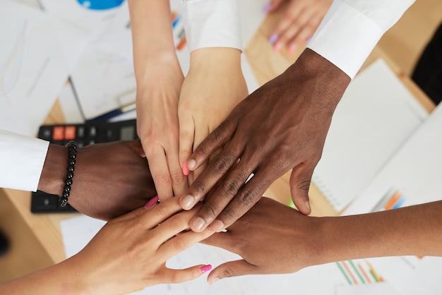 Vista superior de primer plano: los empleados multinacionales ponen sus manos en una pila, mostrando apoyo y unidad, juntos hacia un objetivo común. equipo exitoso.
