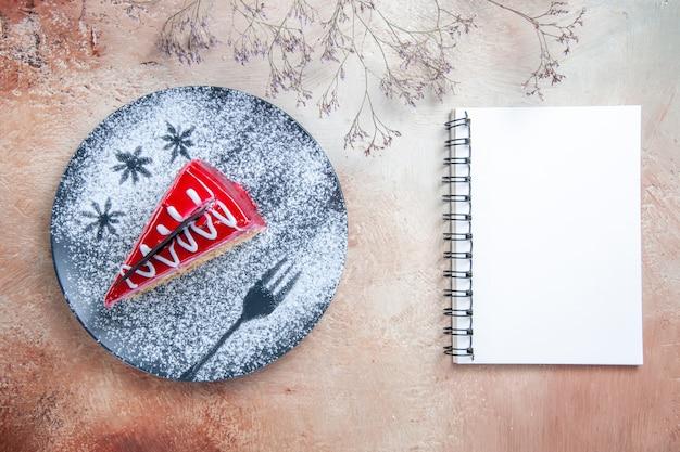 Vista superior de primer plano pastel un apetitoso pastel en el plato cuaderno blanco