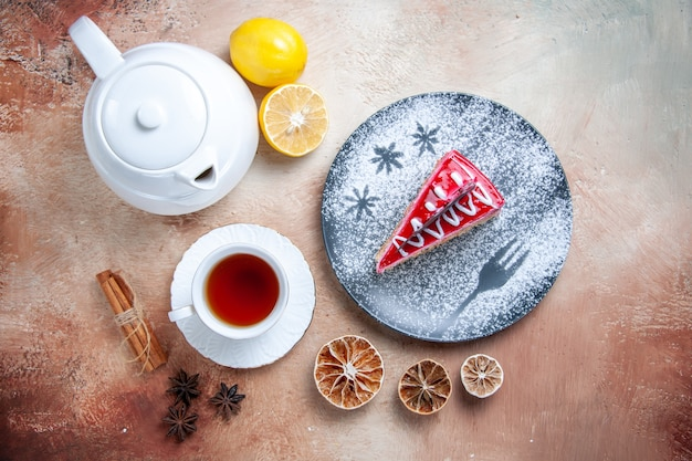 Vista superior de primer plano un pastel blanco taza de té un pastel tetera limón canela en rama