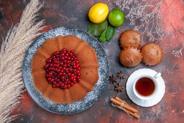 Vista superior de primer plano pastel de cupcakes con cupcakes de grosellas rojas una taza de té de anís estrellado