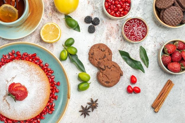 Vista superior de primer plano pastel de fresa plato de pastel de fresas y semillas de granada una taza de té galletas de frutas cítricas anís estrellado sobre la mesa