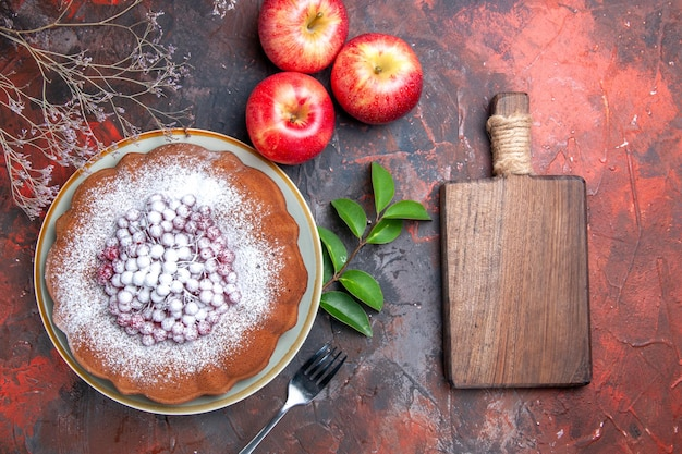 Vista superior de primer plano pastel un pastel con bayas tenedor manzanas deja la tabla de cortar