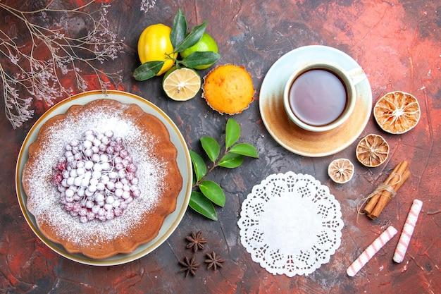 Vista superior de primer plano pastel un pastel una taza de té tapete de encaje limón anís estrellado cupcake palitos de canela