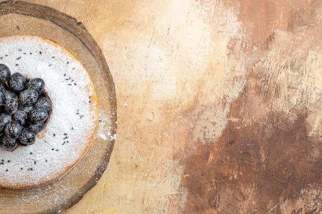 Vista superior de primer plano pastel un pastel con uvas negras en la tabla de cortar