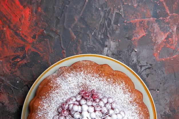 Vista superior de primer plano un pastel un plato de pastel con grosellas rojas y azúcar en polvo