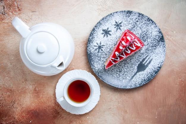 Vista superior de primer plano un pastel taza de té blanco una tetera de pastel