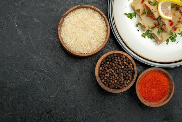 Vista superior de primer plano plato blanco de repollo relleno con hierbas limón y salsa en un plato blanco y cuencos de especias coloridas, pimienta negra y arroz en la mesa
