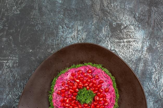Vista superior de primer plano plato de navidad plato de navidad con hierbas semillas de granada