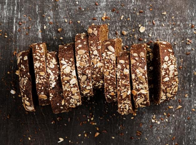 Vista superior de primer plano rebanadas de pan integral y fondo de madera