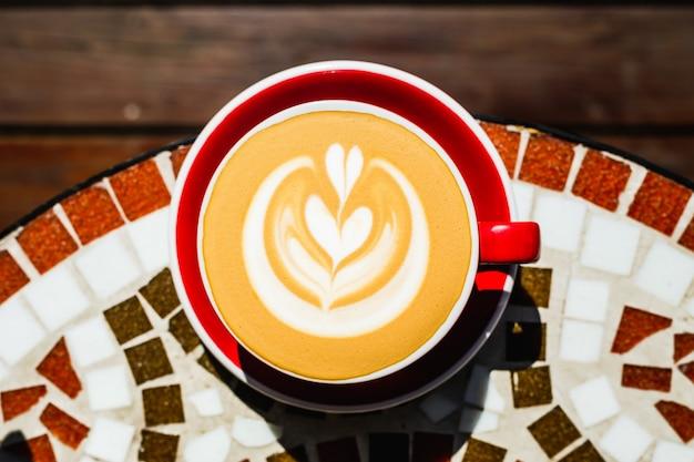 Una vista superior de primer plano de la taza de café capuchino rojo recién hecho en una mesa de piedra de mosaico de una terraza de café en un día soleado