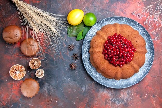 Vista superior de primer plano una taza de té cupcakes limón pastel de anís estrellado en el plato ramas espigas de trigo