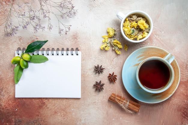 Vista superior de primer plano una taza de té una taza de té canela en rama cuaderno de hierbas