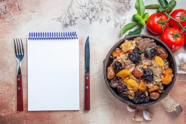 Vista superior de primer plano tomates pilaf ajo tazón de pilaf en el tablero tenedor cuchillo cuaderno blanco