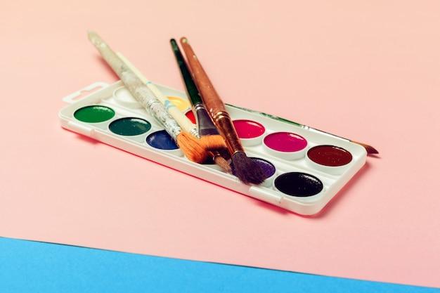 Vista superior del proceso de trabajo papel de acuarela en blanco, suministros de pintura de acuarela, pinceles