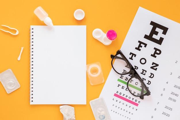 Vista superior de productos de consulta óptica con maqueta de cuaderno