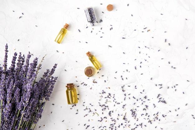 Vista superior de productos de cuidado corporal de aceite de lavanda con luz solar. concepto de aromaterapia, spa y cuidado de la salud natural, plano