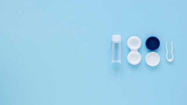 Vista superior de productos para el cuidado de los ojos sobre fondo azul con espacio de copia