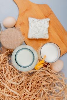 Vista superior de los productos lácteos como queso cottage en rebanadas de pan en la tabla de cortar crema de leche y huevos con paja sobre fondo azul.