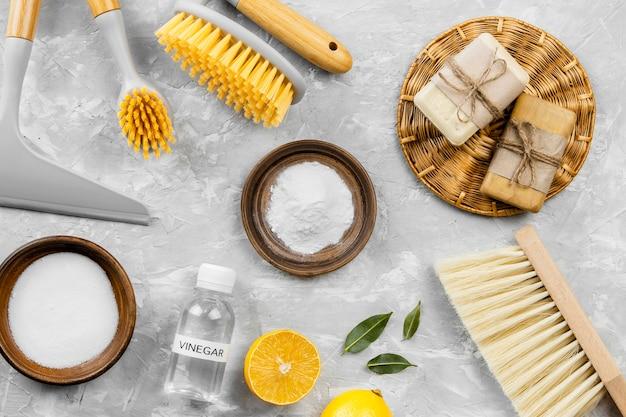 Vista superior de productos de limpieza ecológicos con bicarbonato de sodio y cepillos.