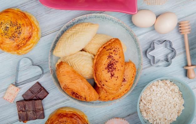 Vista superior de productos de panadería como badambura shakarbura goghal en placa huevos copos de avena de chocolate en la mesa de madera