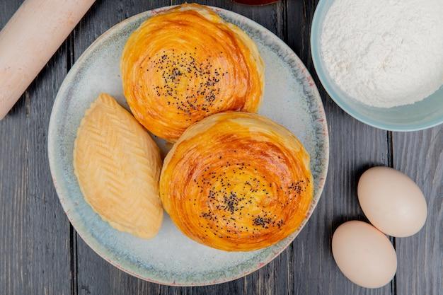 Vista superior de productos de panadería como shakarbura goghal en plato con harina de huevos en la mesa de madera