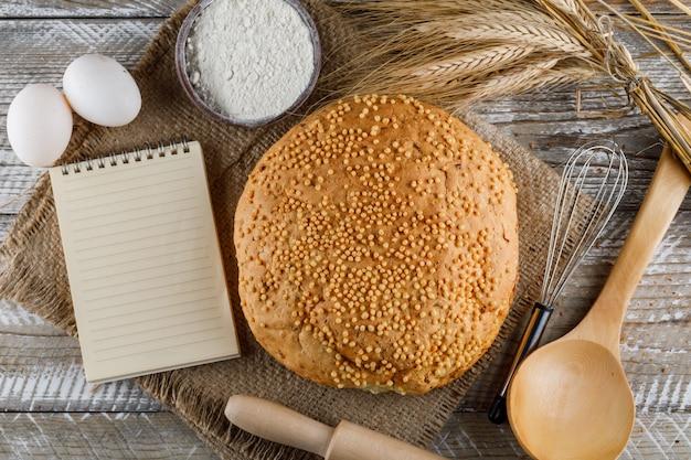 Vista superior de productos de panadería con huevos, rodillo, bloc de notas, cuchara, harina en la superficie de madera. horizontal