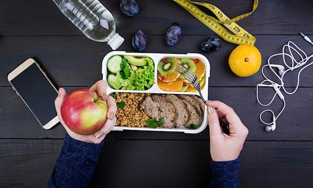 Vista superior que muestra las manos comiendo un almuerzo saludable con bulgur, carne, verduras frescas y fruta