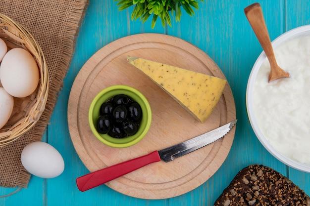 Vista superior de queso con aceitunas y un cuchillo sobre un soporte con yogur en un recipiente sobre un fondo turquesa