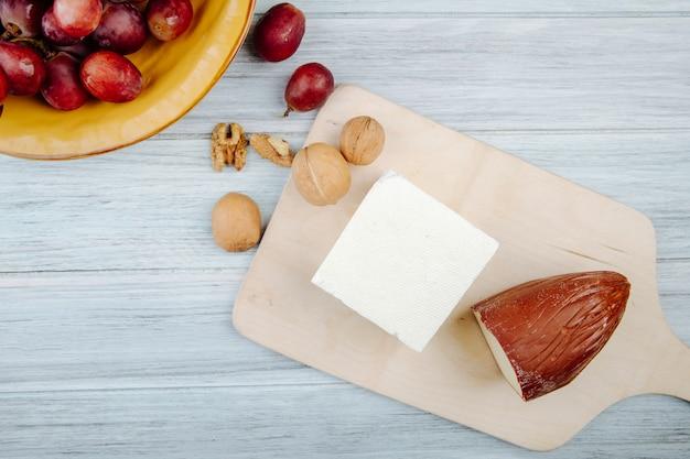 Vista superior de queso ahumado y queso feta sobre una tabla de cortar de madera con nueces y uvas dulces en mesa rústica