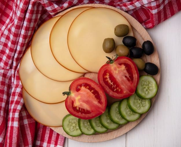 Vista superior de queso ahumado con tomates, pepinos y aceitunas en un soporte con una toalla a cuadros roja sobre un fondo blanco.
