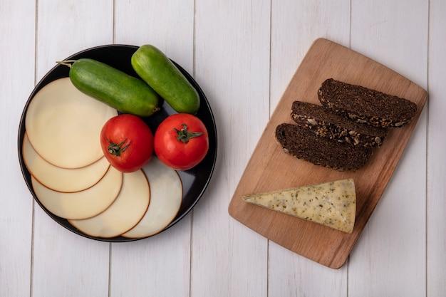 Vista superior de queso ahumado con tomates y pepinos en un plato con rebanadas de pan negro sobre un soporte sobre un fondo blanco.