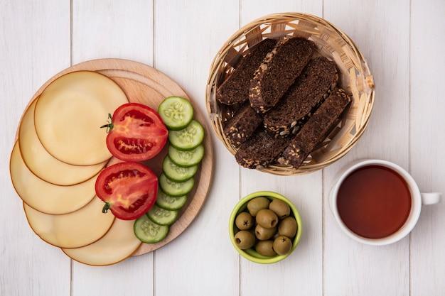 Vista superior de queso ahumado con tomates pepinos sobre un soporte con aceitunas rebanadas de pan negro y una taza de té sobre un fondo blanco.