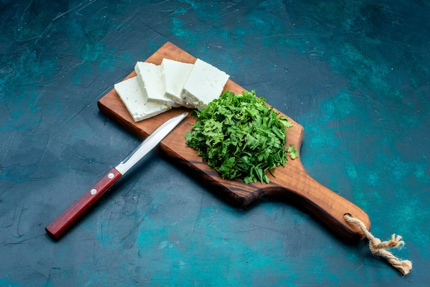 Vista superior de queso blanco con verduras frescas sobre superficie azul oscuro
