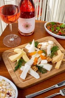 Una vista superior de queso blanco con verduras y vino en la mesa, comida, desayuno