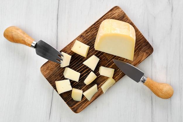 Vista superior de queso de cabra cortado en trozos sobre tabla para cortar madera