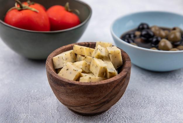 Vista superior de queso en un cuenco de madera con tomates frescos y aceitunas sobre un fondo blanco.