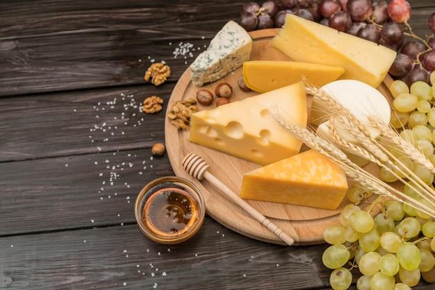 Vista superior de queso gourmet con miel y uvas