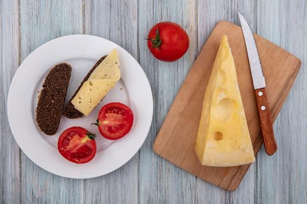 Vista superior de queso maasdam con un cuchillo sobre un soporte con tomates y rebanadas de pan negro en un plato sobre un fondo gris