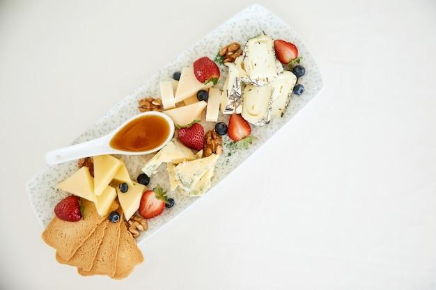 Vista superior de queso con miel, nueces, fresas y tostadas