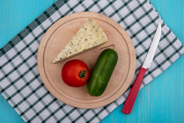 Vista superior de queso con pepino y tomate en un soporte con un cuchillo sobre una toalla a cuadros sobre un fondo turquesa