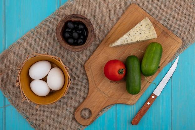 Vista superior de queso con pepinos y tomate en una tabla de cortar con un cuchillo huevos de gallina y aceitunas en una servilleta beige