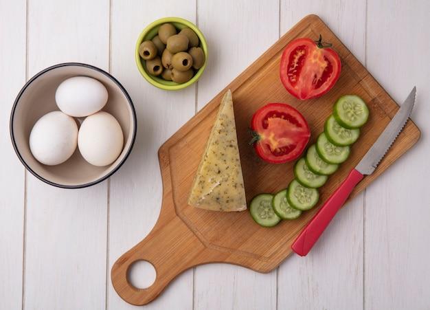 Vista superior de queso con tomate, pepino y aceitunas con un cuchillo en un soporte con aceitunas y huevos de gallina sobre un fondo blanco.