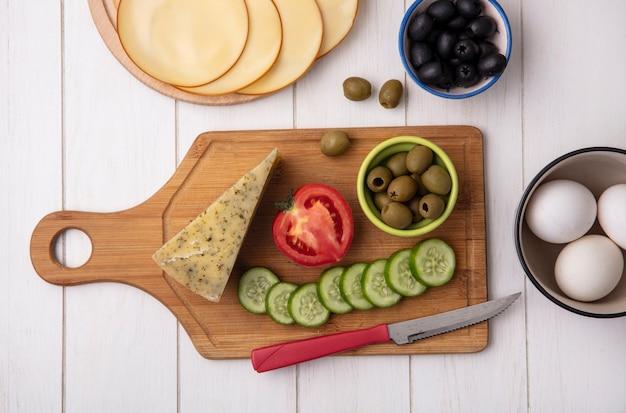 Vista superior de queso con tomate, pepino y aceitunas con un cuchillo en un soporte con huevos de gallina sobre un fondo blanco.