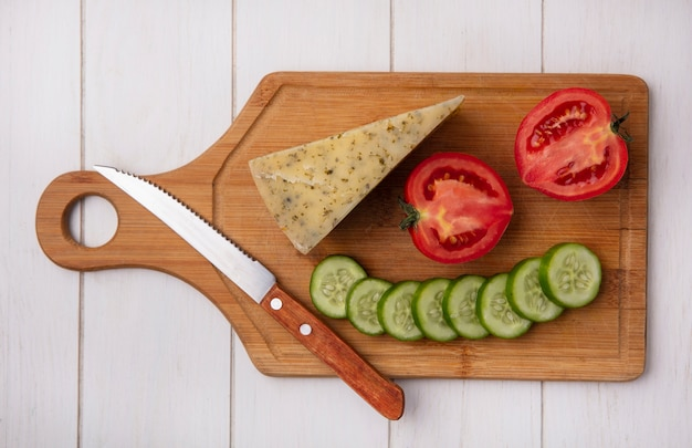 Vista superior de queso con tomate pepino y cuchillo sobre un soporte sobre un fondo blanco.