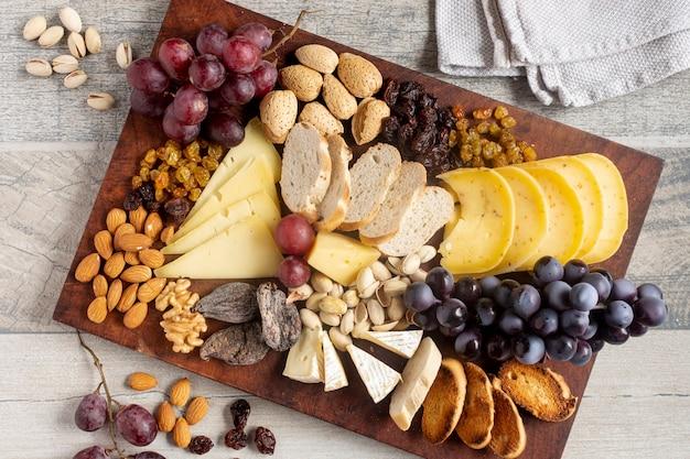 Vista superior de queso con uvas y nueces