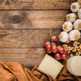Vista superior de queso; uvas rojas; nogal y ajo sobre mesa de madera.